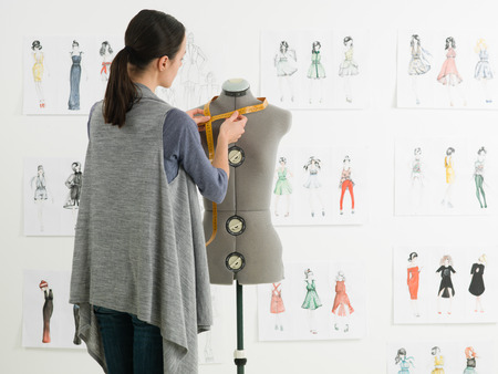 textile industry: young caucasian female fashion designer taking measurements on mannequin in her studio