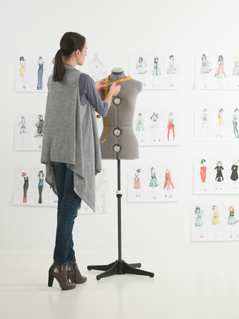 artists dummy: young caucasian female fashion designer taking measurements on mannequin in her studio