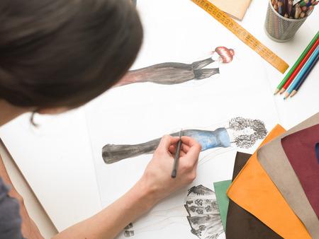 upper view of fashion designer sitting at desk, sketching in her atelier