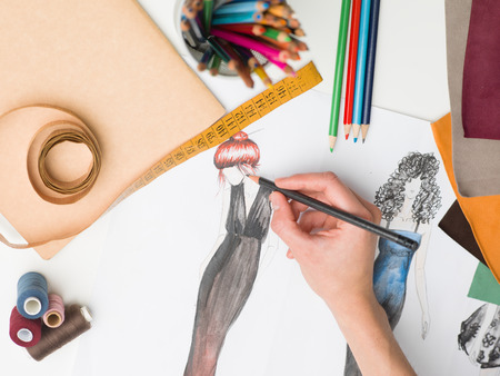 designer clothes: female hand drawing fashion sketch on desk with designing equipment