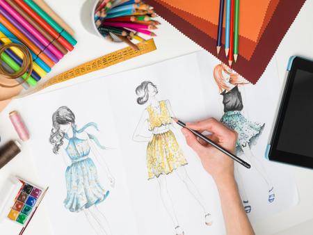 설계 장비와 책상에 여성의 손을 그리기 패션 스케치