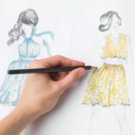 couturier: closeup of human hand drawing fashion design on paper Stock Photo