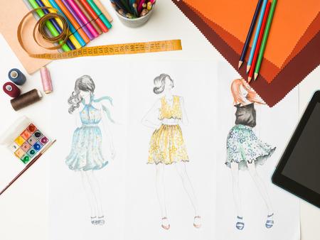 bovenaanzicht van een bureau met mode ontwerpen apparatuur en schetsen Stockfoto