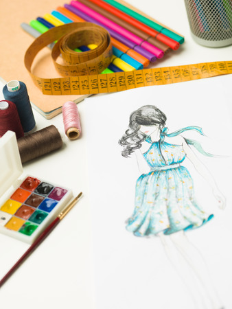 designing: closeup of fashion designer workspace with sketches and designing equipment Stock Photo