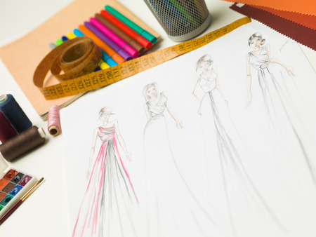 evening gowns: closeup of fashion designer workspace with sketches of evening gowns and designing equipment Stock Photo