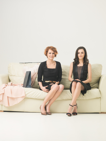 two happy female friends in little black dresses sitting on sofa, happy after shopping. copy space available photo