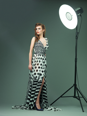 evening gown: beautiful fashion model in evening gown, standing and posing near studio light flashes