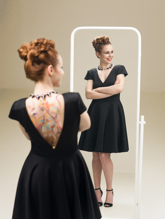 woman in the mirror: beautiful red headed woman in fancy black dress standing in front of mirror looking happy Stock Photo