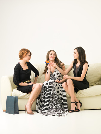 lending: women out shopping, sitting on sofa and lending money to one of them to buy dresses. copy space avaiable