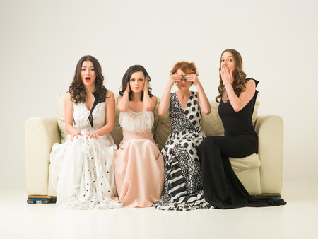 group of beautiful women sitting on sofa and posing as hear no evil, see no evil, speak no evil