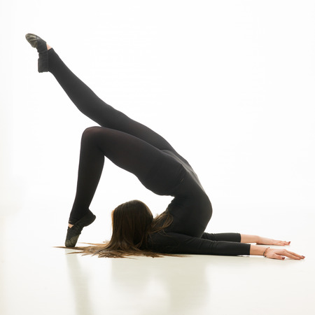 contortionist: young flexible woman doing gymnastics exercise, on white background
