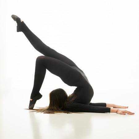acrobatic: young flexible woman doing gymnastics exercise, on white background