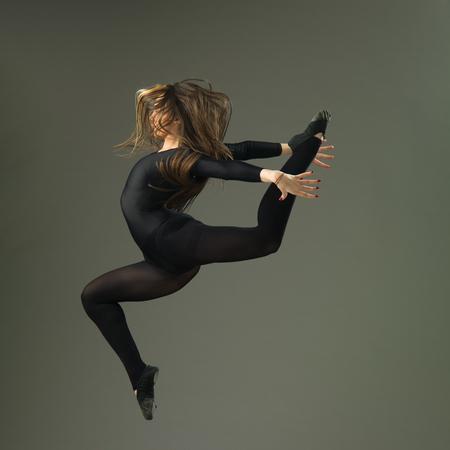 female dancer jumping against grey background
