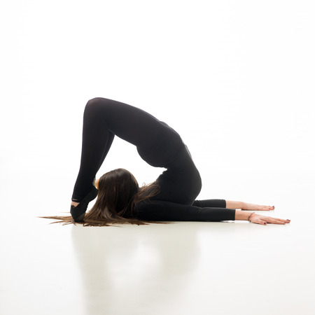 incredible: young flexible woman doing gymnastics exercise, on white background