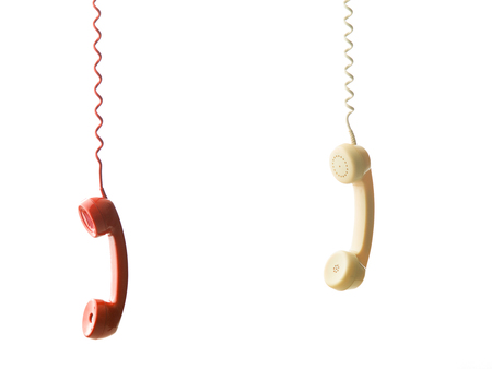 hangup: two different handsets from vintage phones hanging, on white background