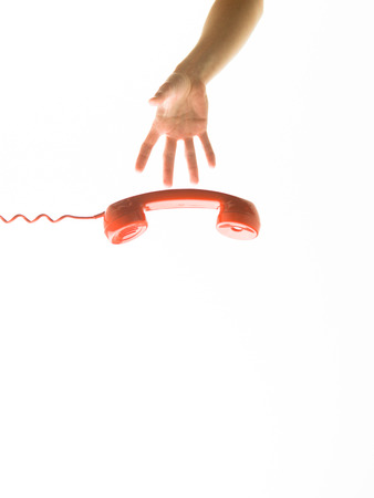 contactus: human hand reaching for red phone receiver, isolated on white background Stock Photo