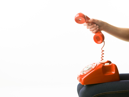 answering phone: woman answering red phone, on white background. copy space available Stock Photo