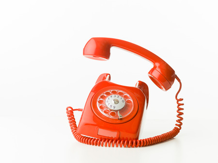 closeup of red vintage phone ringing, isolated on white background
