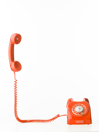 rotary dial telephone: retro styled telephone with receiver standing up, isolated on white background