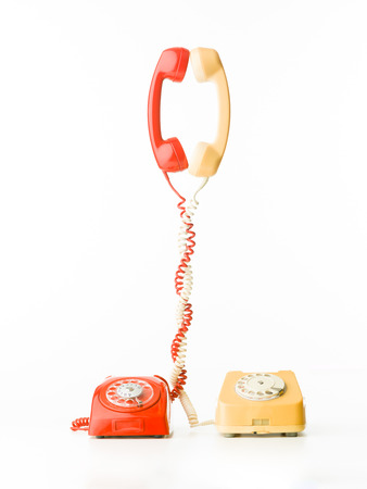 two vintage phones with handsets and cables tangled together, on white background photo