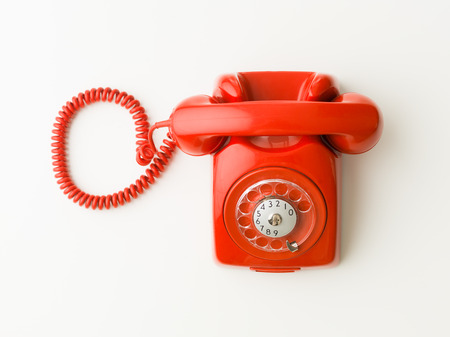 rotary dial telephone: top view of red vintage phone on white background