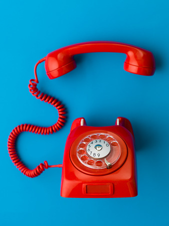 red vintage phone with handset off the hook, on blue background Foto de archivo