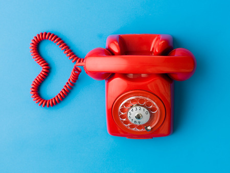 customercare: upper view of red phone with heart shape made out of its cable, on blue background