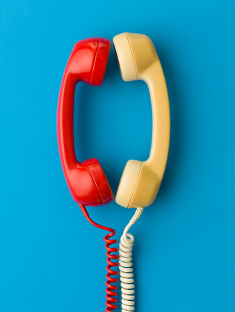 hangup: two handsets facing each other and talking on blue background Stock Photo