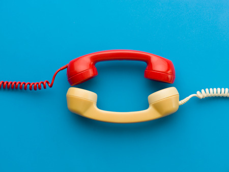 hangup: two handsets facing each other on blue background