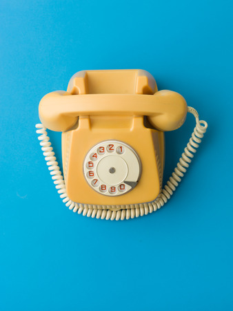 upper view of yellow vintage phone on blue background