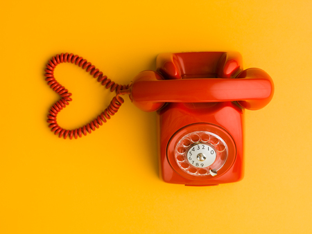 upper view of red phone with heart shape made out of its cable, on yellow background Standard-Bild