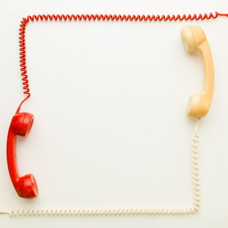 hangup: two handsets from vintage phones facing each other arranged in a square shape, on white background Stock Photo