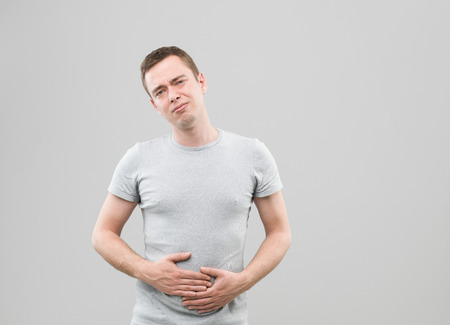 upset stomach: front view of young caucasian man with upset stomach Stock Photo