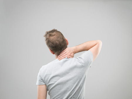 studioshot: rear view of man experiencing neck pain Stock Photo