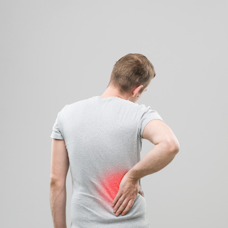 stretching condition: rear view of man experiencing back pain, with red spot marking the injured area
