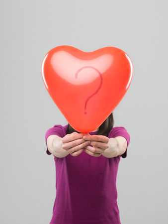 studioshot: caucasian woman holding heart shaped balloon with question mark in front of her head, against grey background Stock Photo