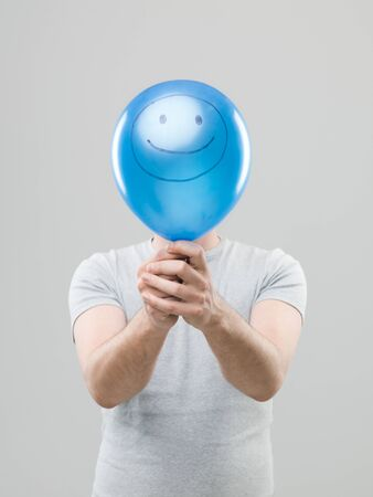 hiding face: man hiding his face behing blue balloon with smiley face drawn on it, on grey background