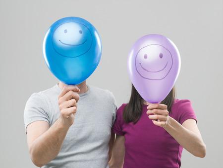 cara sonriente: pareja esconde detrás de sus cabezas globos de colores con caras sonrientes, contra el fondo gris Foto de archivo