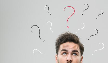 pensamiento creativo: Pensamiento del hombre con muchos signos de interrogación sobre su cabeza, contra el fondo gris