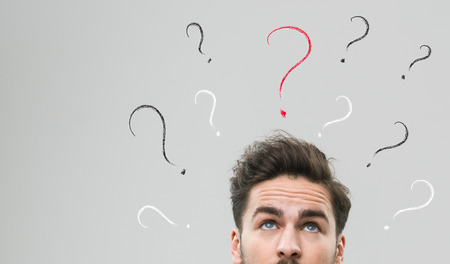 man think: thinking man with many question marks above his head, against grey background Stock Photo