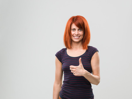 handsign: portrait of happy woman giving thumbs up. copy space available