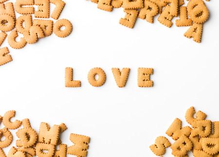 galletas: amar palabra escrita con galletas de letras, sobre fondo blanco Foto de archivo
