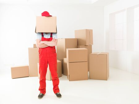 deliveryman: front view of deliveryman standing in new house with arms crossed against his chest, box covering his head Stock Photo