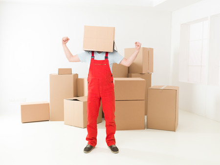deliveryman: fattorino estatico tenendo le braccia in alto, in piedi nella nuova casa con scatola copre la testa Archivio Fotografico
