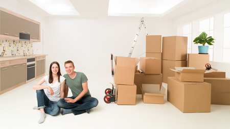 moving in: young happy couple sitting on floor in new apartment with moving boxes around them