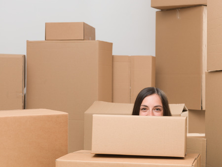 cardboard only: happy woman surounded by cardboard boxes only seeing half of her head