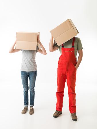 boite carton: femme et homme debout et tenant des boîtes en carton au-dessus de leurs têtes, sur fond blanc. copie espace disponible