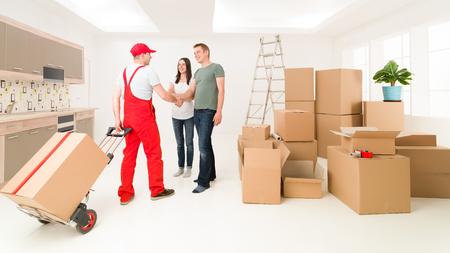 home moving: couple moving in new home and receiving package from delivery man