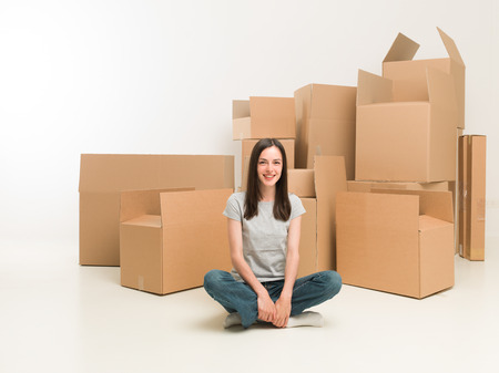 homeownership: happy young woman sitting on floor surrounded by moving boxes Stock Photo