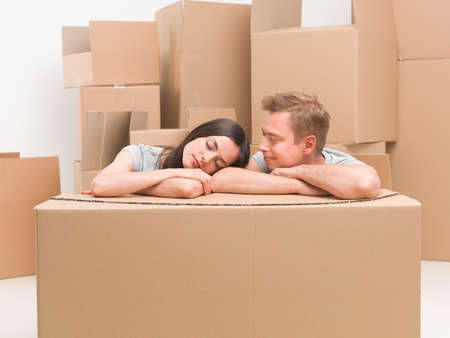 moving box: young caucasian couple resting on cardoard box after moving in house